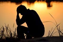 Deprimierter Mann, der auf Hände sitzt Stockbilder