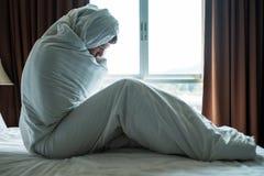 Deprimierter Mann, der auf seinem Bett bedeckt mit Decke sitzt und Fenster betrachtet Er ist nach Scheidung deprimiert Lizenzfreie Stockbilder
