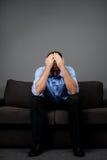 Deprimierter Mann, der auf Sofa sitzt Stockfotografie