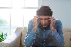 Deprimierter Mann, der auf Sofa sitzt Lizenzfreie Stockbilder