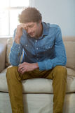 Deprimierter Mann, der auf Sofa sitzt Lizenzfreie Stockfotografie