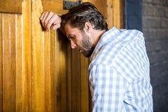 Deprimierter Mann, der auf Tür sich lehnt Stockbilder