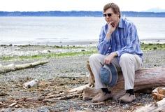 Deprimierter Mann, der auf Treibholz auf Strand sitzt Lizenzfreie Stockfotografie