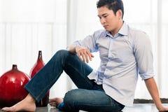 Deprimierter Mann, der auf Wohnungsboden sitzt Stockbilder