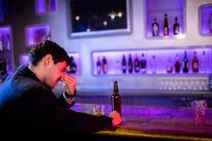 Deprimierter Mann, der Bier am Barzähler isst Stockfotografie