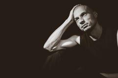 Deprimierter Mann, der in der Dunkelheit mit Leere in seinen Augen sitzt Lizenzfreie Stockfotos