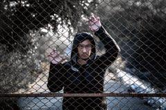 Deprimierter Mann, der einen schwarzen Hoodie steht hinter einem Zaun Han trägt Lizenzfreie Stockfotografie