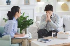 Deprimierter Mann, der emotional an der Psychotherapeutsitzung spricht lizenzfreie stockfotografie