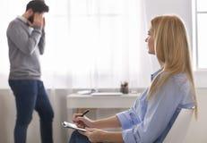 Deprimierter Mann, der emotional an der Psychotherapeutsitzung spricht stockfoto