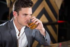 Deprimierter Mann, der Glas Whisky am Zähler isst Lizenzfreies Stockfoto
