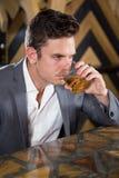 Deprimierter Mann, der Glas Whisky am Zähler isst Lizenzfreie Stockfotos