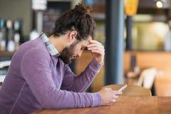 Deprimierter Mann, der Handy im Restaurant hält Stockfotografie