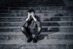 Deprimierter Mann, der heraus Seiten auf den Schritten sich fühlen ermüdet und traurig sitzt Lizenzfreie Stockbilder