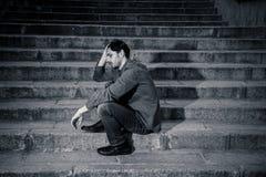 Deprimierter Mann, der heraus Seiten auf den Schritten sich fühlen ermüdet und traurig sitzt Stockfotografie