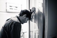 Deprimierter Mann, der heraus zu Hause ein Fenster im Konzept der psychischen Gesundheit schaut Lizenzfreie Stockbilder