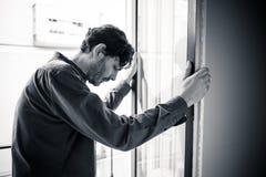Deprimierter Mann, der heraus zu Hause ein Fenster im Konzept der psychischen Gesundheit schaut Stockbilder