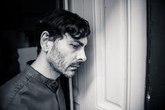 Deprimierter Mann, der heraus zu Hause ein Fenster im Konzept der psychischen Gesundheit schaut Lizenzfreie Stockfotos