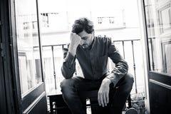 Deprimierter Mann, der heraus zu Hause ein Fenster im Konzept der psychischen Gesundheit schaut Lizenzfreies Stockbild