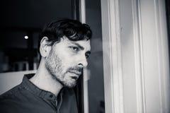Deprimierter Mann, der heraus zu Hause ein Fenster im Konzept der psychischen Gesundheit schaut Stockfoto