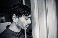Deprimierter Mann, der heraus zu Hause ein Fenster im Konzept der psychischen Gesundheit schaut Lizenzfreies Stockfoto