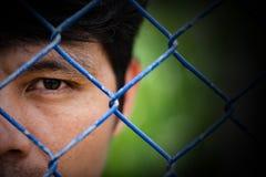 Deprimierter Mann, der hinter einem Zaun, Abschluss oben auf Gesicht steht Stockfoto