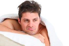 Deprimierter Mann, der im Bett liegt Lizenzfreie Stockfotos