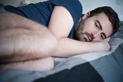 Deprimierter Mann, der im Bett sich fühlt schlecht liegt Lizenzfreie Stockbilder