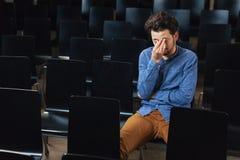 Deprimierter Mann, der im Konferenzsaal sitzt Lizenzfreie Stockbilder