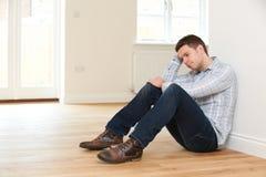 Deprimierter Mann, der im leeren Raum des wieder eingesetzten Hauses sitzt Stockfotografie