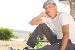 Deprimierter Mann, der mit einer Flasche Weißwein sitzt Stockfotos