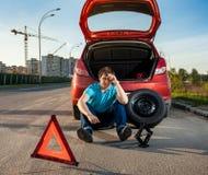 Deprimierter Mann, der nahe Auto mit durchbohrtem Reifen sitzt Lizenzfreies Stockfoto