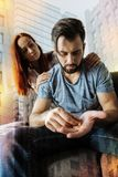 Deprimierter Mann, der Pillen während seine Freundin glaubt gesorgt hält Lizenzfreie Stockbilder