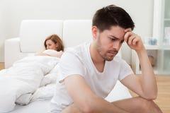 Deprimierter Mann, der am Rand des Betts sitzt Stockbilder