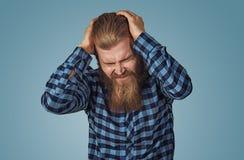 Deprimierter Mann, der sehr starken Kopfschmerzen hat lizenzfreie stockfotografie