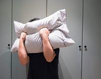 Deprimierter Mann, der sein Gesicht mit Kissen bedeckt und in ANG schreit Stockbild