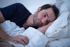 Deprimierter Mann, der in seinem Bett liegt Lizenzfreies Stockbild