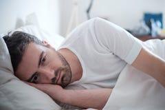 Deprimierter Mann, der in seinem Bett liegt und schlecht sich fühlt Stockbild