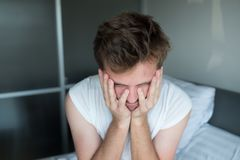 Deprimierter Mann, der in seinem Bett sitzt und schlecht sich fühlt Lizenzfreies Stockbild
