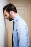 Deprimierter Mann, der seinen Kopf auf Wand lehnt Stockfotos