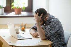 Deprimierter Mann, der in seiner Laptop-Computer empfängt schlechte Nachrichten schaut Lizenzfreie Stockfotos