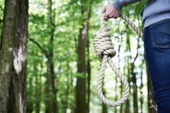 Deprimierter Mann, der Selbstmord durch das Hängen im Wald erwägt Lizenzfreie Stockbilder