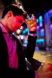 Deprimierter Mann, der Whisky am Stangenzähler isst Lizenzfreie Stockbilder