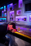 Deprimierter Mann, der Whisky am Stangenzähler isst Lizenzfreies Stockfoto