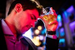 Deprimierter Mann, der Whisky am Stangenzähler isst Stockfotografie