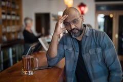 Deprimierter Mann, der am Zähler sitzt Stockfotos