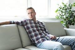 Deprimierter Mann, der zu Hause auf dem Sofa allein denkt Stockfotografie