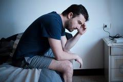 Deprimierter Mann gesetzt auf dem Bett, das schlecht sich fühlt Stockbild