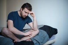 Deprimierter Mann gesetzt auf seinem Bett Stockfotos