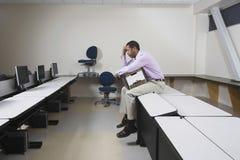 Deprimierter Mann mit dem beweglichen Kasten, der auf Schreibtisch sitzt Stockfotos