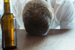 Deprimierter Mann mit Kopf unten auf einem Stangenzähler Stockfotografie
